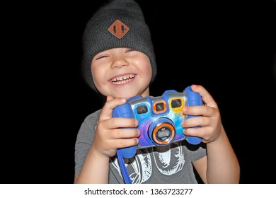 The boy laughs with a camera in his hands.