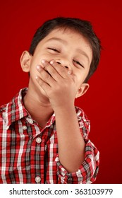 Boy laughs with his mouth closed by in a red background