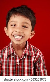 Boy laughs with his mouth in a red background