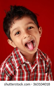 Boy laughs with his tongue out in a red background