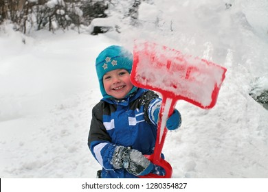 The boy laughs and throws snow with a shovel.