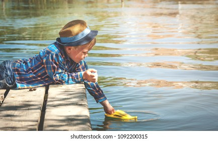 Boy launch toy ship or boat from old wooden pier in the lake. Vacation concept. Boy on wood bridge on lake at sunny day.