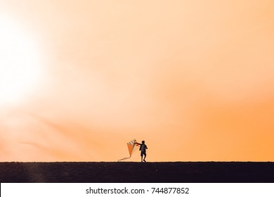 boy launching a kite. silhouette of a child with a kite in hands on a sunset background. Happy time of childhood. The concept of future. Copy space for your text
