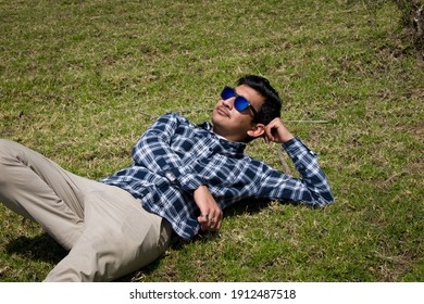 boy laying down on green grass field and looking upward wearing blue sunglasses.