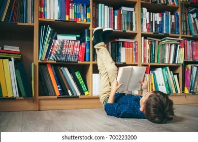 Menino deitado no chão com os pés para cima, lendo um livro contra estante multicolorido na biblioteca. Educação, Conhecimento, Livraria, Palestra. O aluno tem um livro nas mãos.