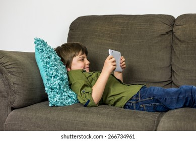 boy laying relaxed on sofa playing on his tablet