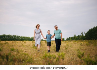 The boy leads the hands of his parents. Happy family in the fresh air. A family of three walking around the field