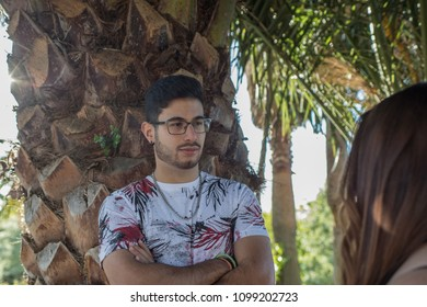 Boy leaning on palm tree with arms crossed