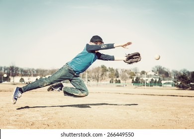 Boy leaping to catch a baseball