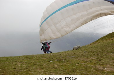 A boy leaps off a mountain to tandem parasail with a pilot