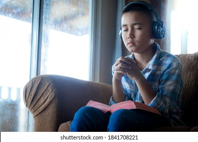 a boy learning bible and praying on sofa at home, listening to the voice of God, religion concept.