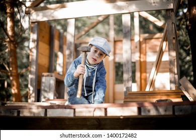 A boy is learning to nail building a tree house. Image with selective focus (on a hammer) and toning