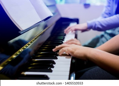 A boy is learning piano with woman teacher and music notation, four hands from two people playing piano, there are musical instrument for learning music, the music learning concept, selective focus.