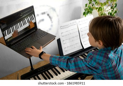 Boy learning to play the piano in distance learning via laptop over the Internet