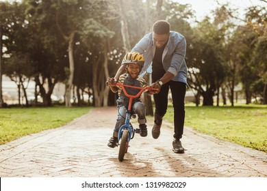 Boy learning to ride a bicycle with his father in park. Father teaching his son cycling at park. - Shutterstock ID 1319982029