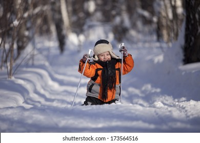 Boy learning to ski. Laughs and falls.