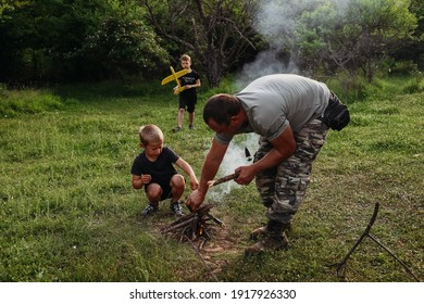 Boy learning to start a bonfire. Father teaching his sons to make a fire. Family camping with kids in fall forest.