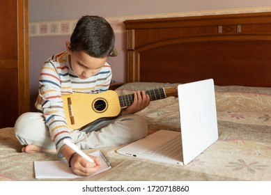 The boy is learning the timple lesson at home from the internet with his laptop. He writes a new song with chords in his notebook. The timple is a typical musical instrument from the Canary Islands
