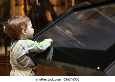 Boy learning touch screen in a museum