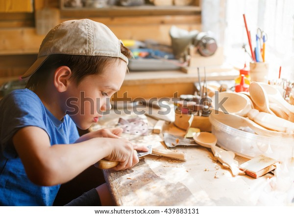 木の彫刻を学ぶ少年。工房で働く若い大工