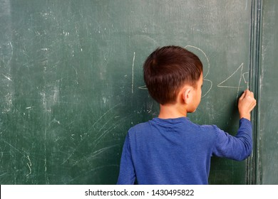 A boy is learning to write down the Arabic numerals on the chalkboard.