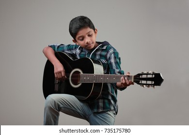 Boy learns to play a guitar