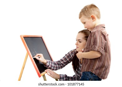 The boy learns write. Young woman shows him how to write on the blackboard. He is standing and gazing attentively to what she was doing.