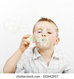 The boy lets go soap bubbles. The little boy and soap bubbles. Carefree.