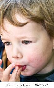 Boy licks fingers after meal-direct behaviour of the litte child