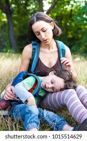 the boy lies with his mother in his arms while traveling through the forest and mountains with backpacks during the holidays. vacation in the forest with a small child. camping in the forest.