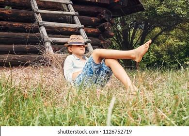 Boy lies near old barn in the garden