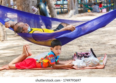 The boy lies on a mat on the beach, his father sleeps in a hammock. Phala Beach, Thailand - 05.20.2020