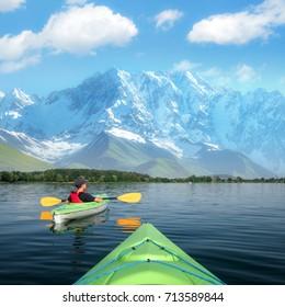 Boy in life jacket on green kayak. Sunny day on wonderful lake. Summer time