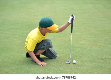 boy lining up a putt on the green