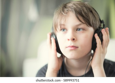 A boy listening to the music or audiobook with headphones