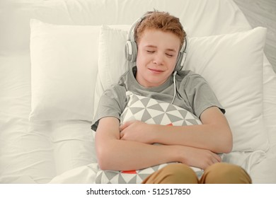 Boy listening music in headphones on bed