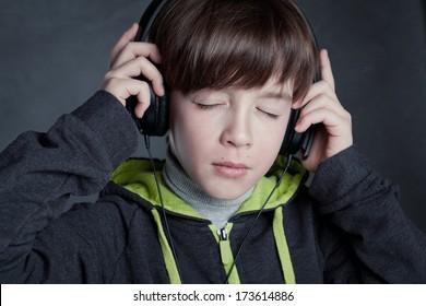 Boy listening to music on headphones, studio