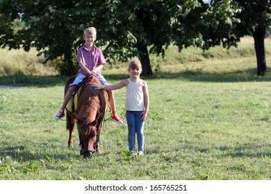 boy and little girl with pony horse