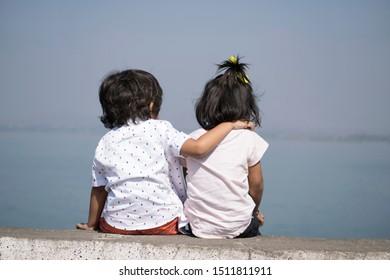 Boy and little girl sitting near lake, Veer dam, Pune, Maharashtra, India
