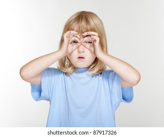 boy with long blond hair looking through fingers as binoculars - isolated on gray