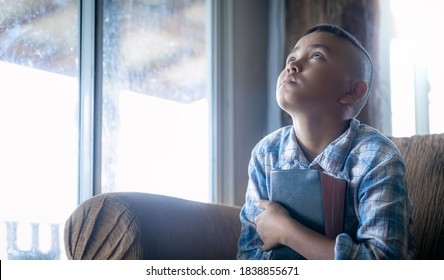 a boy look up and embrace bible, listening to the voice of God, religion concept.
