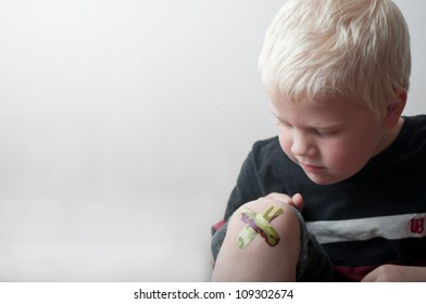 boy looking at band aid on knee