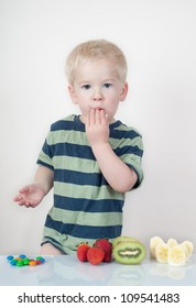 boy looking at camera with hand over mouth with snacks layed out on table