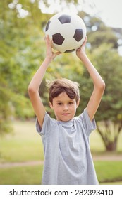 Boy looking at camera and holding a soccer ball in the park on a sunny day
