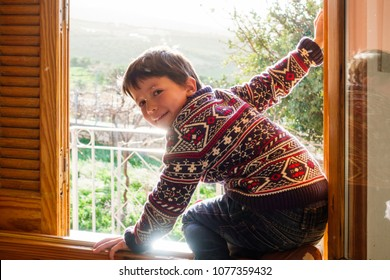 Boy looking at camera while sitting on the window, Greece