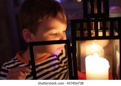 Boy looking at candle in a cafe