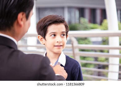 Boy looking to father with attractive smile. Father set up outfit for kid and prepare he to go to school.