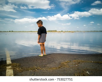 A boy looking at a flooded street
