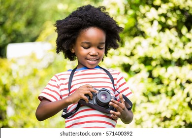 Boy looking at his camera in a park