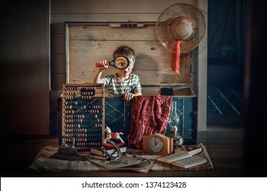 A boy is looking for interesting stuff in old chest, finding a magnifier and look through it with very surprised face expression.His eye in magnifier is very big. Image with selective focus and toning